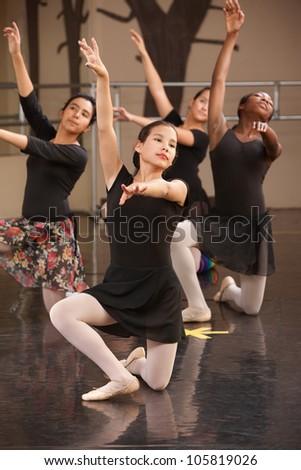 Four young ballet performers kneeling on floor