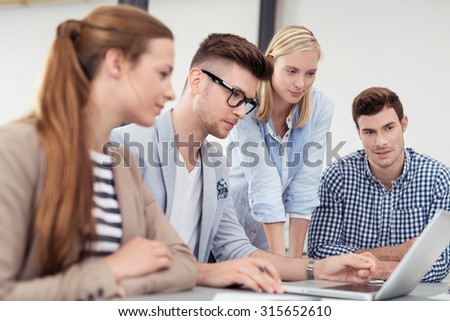 Four Young Businessmen Looking at the Laptop Screen Together While Having a Meeting Inside the Boardroom.