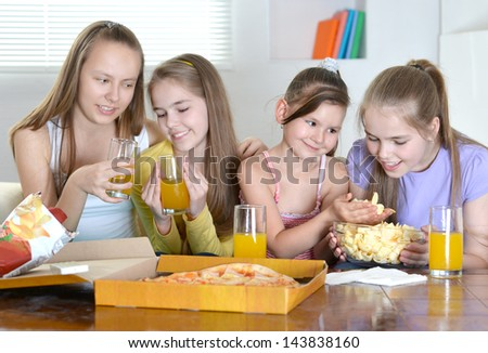 Four young cheerful girls relaxing at home together