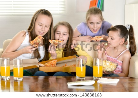 Four young cheerful girls watching TV together