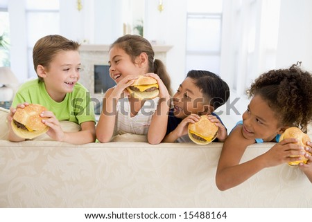 Four young children eating cheeseburgers in living room smiling