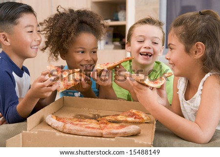Four young children indoors eating pizza smiling