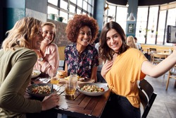 Four Young Female Friends Meeting For Drinks And Food Posing For Selfie In Restaurant