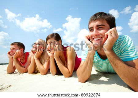 Four young friends lying on sand and smiling