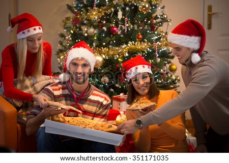 Four young friends sharing pizza and wearing Santa hats while sitting in front of the Christmas tree #351171035