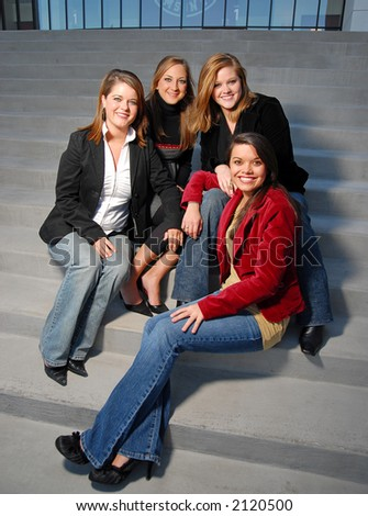 four young girls in business attire on steps