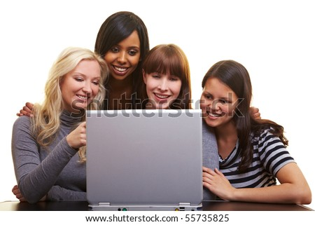Four young happy woman centered around a laptop