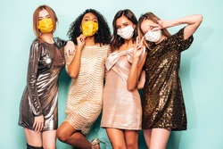 Four young international beautiful brunette women in trendy summer  shiny dress.Sexy female posing near blue wall in studio.Fashionable models with evening makeup. Wearing protective medical masks