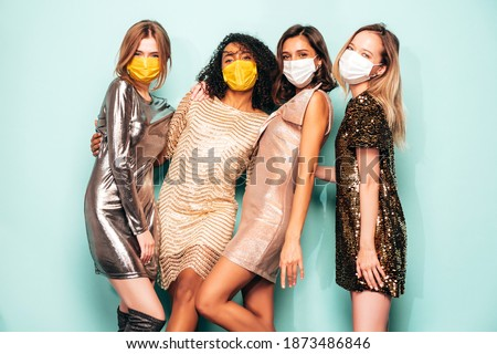 Four young international beautiful brunette women in trendy summer  shiny dress.Sexy female posing near blue wall in studio.Fashionable models giving air kiss. Wearing protective medical masks