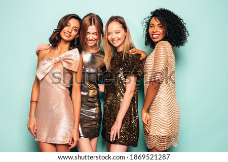 Four young international beautiful brunette women in trendy summer  shiny dress.Sexy smiling carefree female posing near blue wall in studio.Fashionable models with bright evening makeup