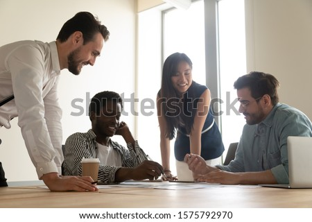 Four young multiracial colleagues financiers gathered in conference room for analyzing company finances sales results make summarizing of financial information together, teamwork brainstorming concept