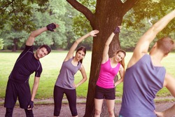Four young people doing aerobics exercises together outdoors in a park , two men and two women, in a healthy active lifestyle concept