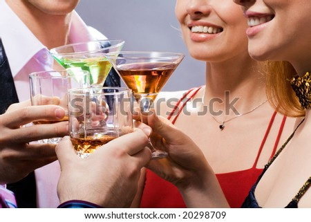 Four young people touch glasses in a toast