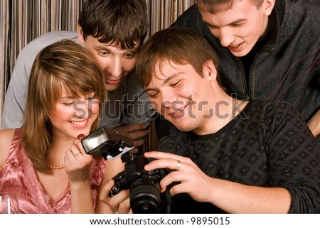 four young smiley men and women with photocamera