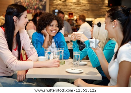 Four young woman college chatting in a coffee shop