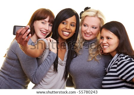 Four young women centered around a cell phone