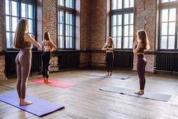 Four young women do complex of stretching yoga asanas in loft style class. Females meditate with closed eyes, back view, Surya namaskar