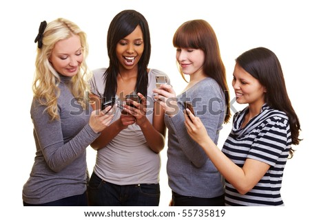 Four young women reading text messages on their cell phones