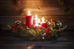 Fourth Advent - Decorated Advent wreath with four red burning candles on a wooden background with festive atmosphere