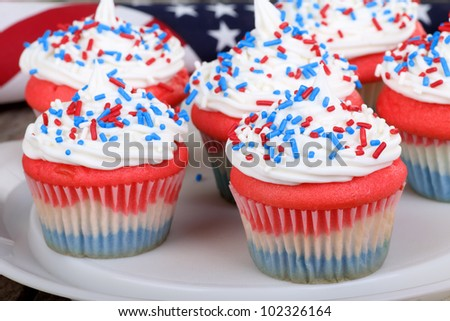 Fourth of july cupcakes on a platter with a flag in background