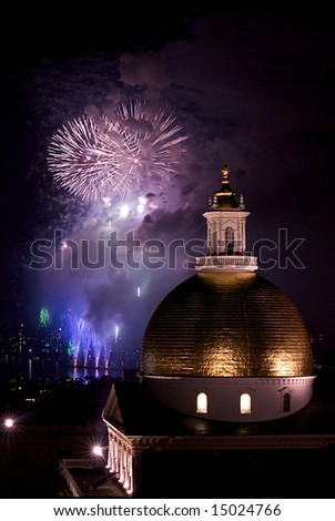 fourth of july fireworks explode in the sky over the charles river with the massachusetts state house in the foreground