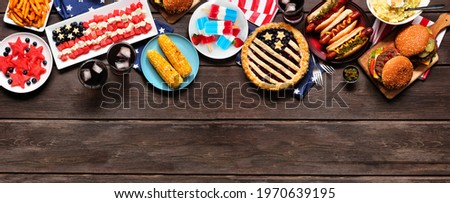 Fourth of July, patriotic, American themed food. Overhead view top border on a dark wood banner background. Copy space. Stock photo ©