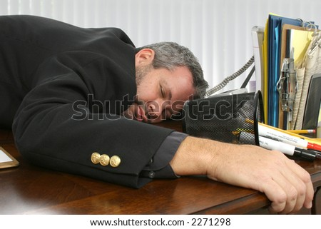 Fourty something business man asleep on desk.