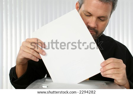 Fourty something business man putting paper into paper shredder.