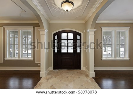 Foyer in new construction home with mahogany wood door