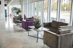 Foyer in the first class lounge with velvet armchairs and square desks with potted orchids
