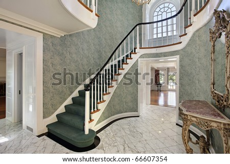 Foyer with green stairs and second floor round window - stock photo