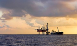 FPSO ship and drilling rig on oil production platform in offshore oil field with beautiful cloud and blue sky background