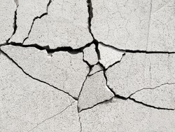 Fractured concrete surface closeup background.