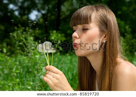 fragile girl blowing a dandelion, which scatters. blowballs