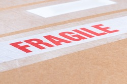 Fragile labeling tape closeup on cardboard packaging