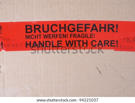 Fragile packet parcel with warning label in English and German - Handle with care, Bruchgefahr