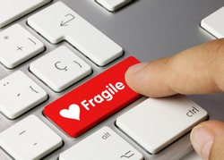 Fragile Written on Red Key of Metallic Keyboard. Finger pressing key.