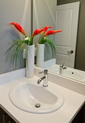 Fragment of a bathroom, washroom with washbasin (sink) and the vase as a decorative element on the counter. Interior design. Vertical.