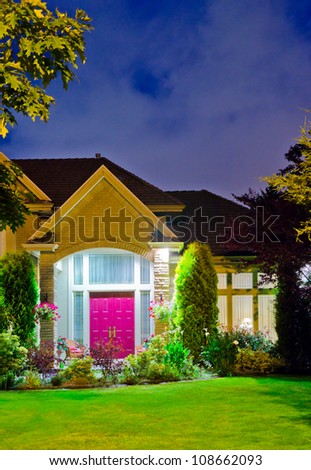 Fragment of a big luxury house with the triple garage doors at dusk, night time.