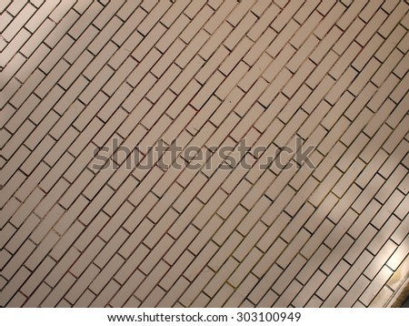Fragment of a brick wall beige with neat rows of brickwork diagonal image. Wall unevenly lit and occupies the entire space of the image. It can be used for background or wallpaper #303100949
