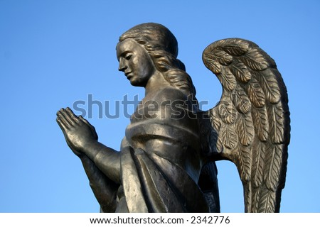 Fragment of a bronze sculpture of a praying angel on a background of the sky a side view,