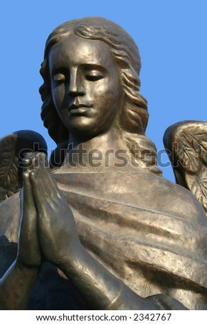Fragment of a bronze sculpture of a praying angel on a background of the sky the front view in details, Isolated