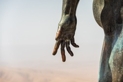 Fragment of a bronze sculpture. Open palm against the sky.
