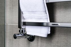fragment of a chrome steel bathroom towel dryer on the gray anthracite tile wall