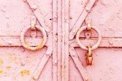 Fragment of a closed old metal door or gate with round knockers and a rusty padlock. Closeup shabby worn texture of iron with pieces of peeling pink paint layer with spots of red rust. Background.
