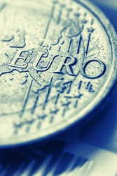 Fragment of a coin of 1 one euro. In focus inscription with the name of the Eurozone currency. Close-up. Vertical dramatic illustration about the European Union. Blue and yellow tinted photo. Macro
