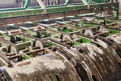 fragment of a conveyor line of sawmill equipment inside a modern lumber mill