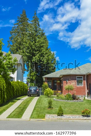 Fragment of a house with traced driveway and parked car on it. Fragment of a house with trees and blue sky on background.