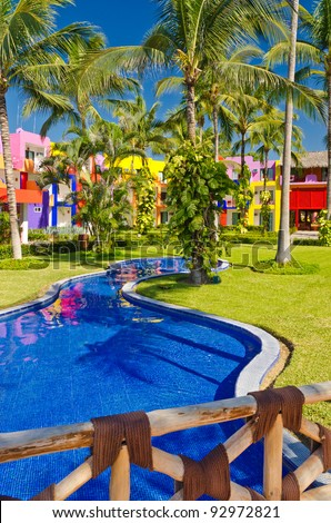 Fragment of a luxury resort with a beautiful pool, fantastic lazy river and nice bridge at sunny day - stock photo