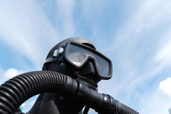 Fragment of a man in a diving suit against the background of the sky. Deep diving equipment on a plastic dummy. Copy space